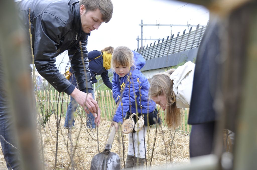 Wethouder Lot van Hooijdonk plant samen met kinderen een nieuw boompje in Tiny Forest 'Eigenwijze Artan' in Utrecht.